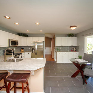 Large farmhouse eat-in kitchen appliance - Example of a large country u-shaped porcelain tile and gray floor eat-in kitchen design in Denver with a double-bowl sink, raised-panel cabinets, white cabinets, granite countertops, subway tile backsplash, stainless steel appliances, gray backsplash and a peninsula