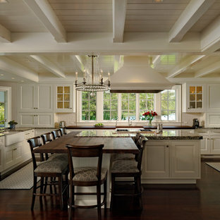 Large traditional eat-in kitchen ideas - Inspiration for a large timeless u-shaped dark wood floor eat-in kitchen remodel in Baltimore with white cabinets, granite countertops, white backsplash, subway tile backsplash, an island, recessed-panel cabinets, paneled appliances and a farmhouse sink