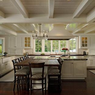 Große Klassische Wohnküche in U-Form mit weißen Schränken, Granit-Arbeitsplatte, Küchenrückwand in Weiß, Rückwand aus Metrofliesen, dunklem Holzboden, Kücheninsel, Schrankfronten mit vertiefter Füllung, Elektrogeräten mit Frontblende und Landhausspüle in Baltimore