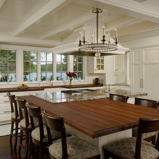 Large traditional eat-in kitchen designs - Example of a large classic u-shaped dark wood floor eat-in kitchen design in Baltimore with a farmhouse sink, white cabinets, granite countertops, white backsplash, subway tile backsplash, an island, recessed-panel cabinets and paneled appliances