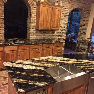 ジャクソンの中サイズのカントリー風おしゃれなアイランドキッチン (エプロンフロントシンク、レイズドパネル扉のキャビネット、淡色木目調キャビネット、大理石カウンター、レンガのキッチンパネル、シルバーの調理設備の、レンガの床、赤い床) の写真