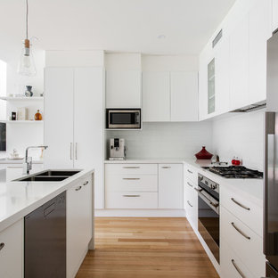 Inspiration for a contemporary u-shaped kitchen in Adelaide with a double-bowl sink, flat-panel cabinets, white cabinets, white splashback, subway tile splashback, stainless steel appliances, medium hardwood floors, a peninsula, brown floor and white benchtop.