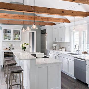 Idee per una grande cucina lineare stile marinaro con lavello sottopiano, ante in stile shaker, ante bianche, elettrodomestici in acciaio inossidabile, parquet chiaro, isola e pavimento marrone