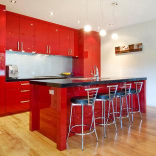 Offene, Zweizeilige, Mittelgroße Moderne Küche mit Doppelwaschbecken, flächenbündigen Schrankfronten, roten Schränken, Quarzwerkstein-Arbeitsplatte, Küchenrückwand in Blau, Glasrückwand, Küchengeräten aus Edelstahl, braunem Holzboden, Kücheninsel und gelbem Boden in Auckland