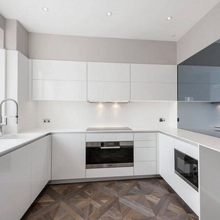 Medium sized contemporary u-shaped enclosed kitchen in London with a submerged sink, flat-panel cabinets, white cabinets, granite worktops, white splashback, stone tiled splashback, stainless steel appliances, medium hardwood flooring and no island.