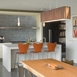 Immagine di una cucina minimalista con elettrodomestici in acciaio inossidabile, ante lisce, paraspruzzi blu e paraspruzzi con piastrelle in ceramica