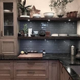 他の地域の大きいエクレクティックスタイルのおしゃれなキッチン (アンダーカウンターシンク、シェーカースタイル扉のキャビネット、グレーのキャビネット、ソープストーンカウンター、グレーのキッチンパネル、ガラスタイルのキッチンパネル、シルバーの調理設備、セラミックタイルの床、茶色い床) の写真