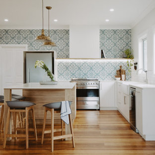 This is an example of a large contemporary l-shaped eat-in kitchen in Hobart with a farmhouse sink, white cabinets, granite benchtops, cement tile splashback, stainless steel appliances, light hardwood floors, with island, white benchtop, flat-panel cabinets, green splashback and brown floor.