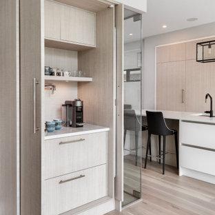 Diseño de cocina contemporánea con armarios con paneles lisos, puertas de armario de madera clara, suelo de madera clara, suelo beige y encimeras blancas