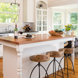 シアトルの中くらいのヴィクトリアン調のおしゃれなキッチン (ドロップインシンク、フラットパネル扉のキャビネット、白いキャビネット、木材カウンター、グレーのキッチンパネル、シルバーの調理設備、淡色無垢フローリング) の写真