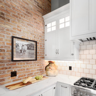 Design ideas for a mid-sized shabby-chic style l-shaped kitchen pantry in Detroit with a farmhouse sink, shaker cabinets, white cabinets, quartz benchtops, beige splashback, mosaic tile splashback, stainless steel appliances, ceramic floors, with island and grey floor.