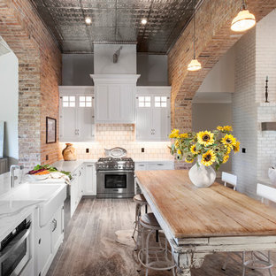 This is an example of a mid-sized shabby-chic style l-shaped kitchen pantry in Detroit with a farmhouse sink, shaker cabinets, white cabinets, quartz benchtops, beige splashback, mosaic tile splashback, stainless steel appliances, ceramic floors, with island and grey floor.