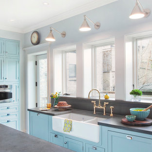 Traditional eat-in kitchen ideas - Example of a classic u-shaped eat-in kitchen design in Chicago with a farmhouse sink, blue cabinets, concrete countertops and stainless steel appliances