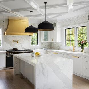 На фото: угловые кухни в современном стиле с врезной раковиной, фасадами с утопленной филенкой, белыми фасадами, разноцветным фартуком, черной техникой, светлым паркетным полом, островом, бежевым полом и разноцветной столешницей