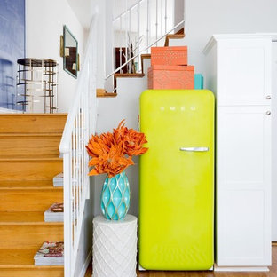 ロサンゼルスの中サイズのエクレクティックスタイルのおしゃれなキッチン (ダブルシンク、シェーカースタイル扉のキャビネット、白いキャビネット、クオーツストーンカウンター、白いキッチンパネル、シルバーの調理設備、淡色無垢フローリング、アイランドなし、茶色い床) の写真