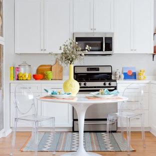 ロサンゼルスの小さいエクレクティックスタイルのおしゃれなキッチン (ダブルシンク、シェーカースタイル扉のキャビネット、白いキャビネット、クオーツストーンカウンター、白いキッチンパネル、シルバーの調理設備の、淡色無垢フローリング、アイランドなし、茶色い床) の写真