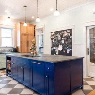Photo of a large eclectic u-shaped eat-in kitchen in San Luis Obispo with a double-bowl sink, shaker cabinets, blue cabinets, multi-coloured splashback, brick splashback, porcelain floors, multiple islands, multi-coloured floor and grey benchtop.