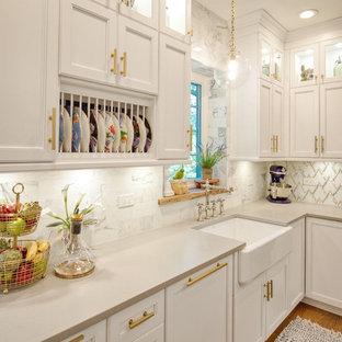 シカゴの大きいエクレクティックスタイルのおしゃれなキッチン (エプロンフロントシンク、落し込みパネル扉のキャビネット、白いキャビネット、クオーツストーンカウンター、白いキッチンパネル、大理石の床、シルバーの調理設備の、無垢フローリング、茶色い床、グレーのキッチンカウンター) の写真