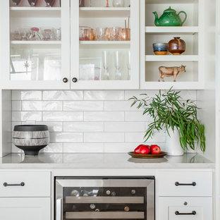 シアトルの大きいエクレクティックスタイルのおしゃれなキッチン (アンダーカウンターシンク、シェーカースタイル扉のキャビネット、白いキャビネット、クオーツストーンカウンター、白いキッチンパネル、磁器タイルのキッチンパネル、シルバーの調理設備、淡色無垢フローリング、茶色い床、グレーのキッチンカウンター) の写真
