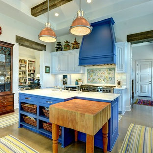 Photo of a large eclectic l-shaped open plan kitchen in Austin with a farmhouse sink, raised-panel cabinets, blue cabinets, stainless steel appliances, concrete floors, grey floor, white benchtop, marble benchtops, multi-coloured splashback, mosaic tile splashback and multiple islands.