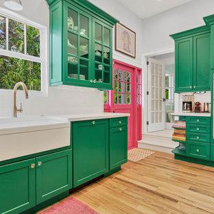 マイアミのコンテンポラリースタイルのおしゃれなコの字型キッチン (エプロンフロントシンク、シェーカースタイル扉のキャビネット、緑のキャビネット、白いキッチンパネル、シルバーの調理設備の、無垢フローリング、アイランドなし、茶色い床、白いキッチンカウンター) の写真