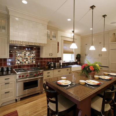 Inspiration for an eclectic kitchen remodel in Minneapolis with paneled appliances, a farmhouse sink, beige cabinets, quartz countertops, red backsplash and ceramic backsplash
