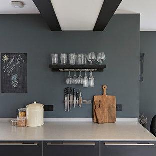 デヴォンの大きいシャビーシック調のおしゃれなキッチン (フラットパネル扉のキャビネット、グレーのキャビネット、ステンレスカウンター、メタリックのキッチンパネル、一体型シンク、シルバーの調理設備の、磁器タイルの床、ベージュの床) の写真