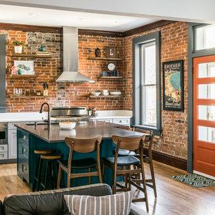 セントルイスの中サイズのインダストリアルスタイルのおしゃれなアイランドキッチン (シングルシンク、シェーカースタイル扉のキャビネット、グレーのキャビネット、クオーツストーンカウンター、レンガのキッチンパネル、シルバーの調理設備の、無垢フローリング、白いキッチンカウンター) の写真