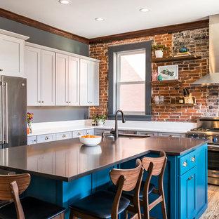 セントルイスの中くらいのエクレクティックスタイルのおしゃれなキッチン (シングルシンク、シェーカースタイル扉のキャビネット、クオーツストーンカウンター、レンガのキッチンパネル、シルバーの調理設備、無垢フローリング、白いキッチンカウンター、青いキャビネット、茶色い床) の写真