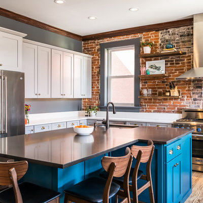 Mid-sized eclectic l-shaped medium tone wood floor and brown floor kitchen photo in St Louis with a single-bowl sink, shaker cabinets, quartz countertops, brick backsplash, stainless steel appliances, an island, white countertops and blue cabinets