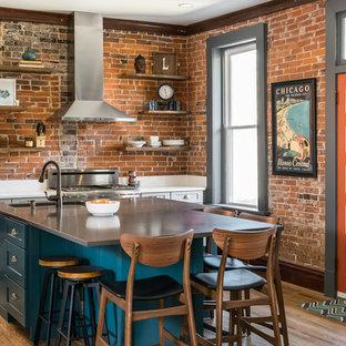 セントルイスの中サイズのエクレクティックスタイルのおしゃれなアイランドキッチン (シングルシンク、シェーカースタイル扉のキャビネット、グレーのキャビネット、クオーツストーンカウンター、レンガのキッチンパネル、シルバーの調理設備の、無垢フローリング、白いキッチンカウンター) の写真