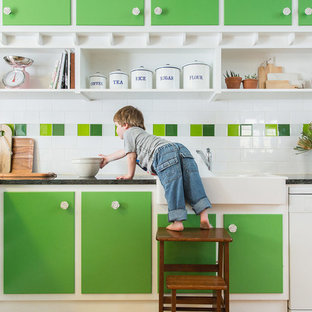 Inspiration for a medium sized eclectic l-shaped kitchen/diner in Adelaide with a belfast sink, green cabinets, marble worktops, multi-coloured splashback, ceramic splashback, white appliances, light hardwood flooring and no island.