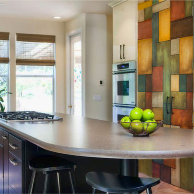Enclosed kitchen - mid-sized eclectic galley porcelain tile enclosed kitchen idea in San Diego with flat-panel cabinets, multicolored backsplash, stainless steel appliances, a single-bowl sink, beige cabinets, quartz countertops, ceramic backsplash and an island