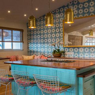 他の地域の大きいエクレクティックスタイルのおしゃれなキッチン (ドロップインシンク、シェーカースタイル扉のキャビネット、白いキャビネット、木材カウンター、青いキッチンパネル、セメントタイルのキッチンパネル、シルバーの調理設備の、無垢フローリング) の写真