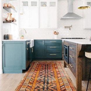 Inredning av ett eklektiskt mellanstort vit vitt kök, med en integrerad diskho, skåp i shakerstil, turkosa skåp, bänkskiva i kvartsit, vitt stänkskydd, stänkskydd i tunnelbanekakel, rostfria vitvaror, ljust trägolv, en köksö och brunt golv