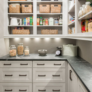 Design ideas for a transitional l-shaped kitchen pantry in St Louis with white cabinets, soapstone benchtops, porcelain floors, open cabinets, grey splashback, black floor and black benchtop.