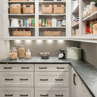 Diseño de cocina en L, clásica renovada, con puertas de armario blancas, encimera de esteatita, suelo de baldosas de porcelana, despensa, armarios abiertos, salpicadero verde, suelo negro y encimeras negras