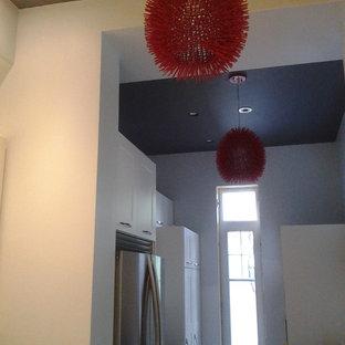モントリオールの中サイズのエクレクティックスタイルのおしゃれなキッチン (シェーカースタイル扉のキャビネット、白いキャビネット、クオーツストーンカウンター、赤いキッチンパネル、ガラスタイルのキッチンパネル、シルバーの調理設備の、ドロップインシンク、磁器タイルの床) の写真