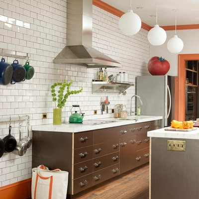 Eclectic galley kitchen photo in New York with flat-panel cabinets, brown cabinets, white backsplash, subway tile backsplash and stainless steel appliances