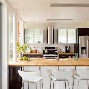 Example of an eclectic galley kitchen design in Portland with stainless steel appliances, wood countertops, flat-panel cabinets and black cabinets