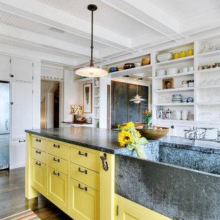 Bild på ett eklektiskt kök, med rostfria vitvaror, en integrerad diskho, öppna hyllor, gula skåp och bänkskiva i täljsten