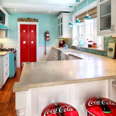 Elegant galley enclosed kitchen photo in Philadelphia with a farmhouse sink, glass-front cabinets, white cabinets, concrete countertops and colored appliances