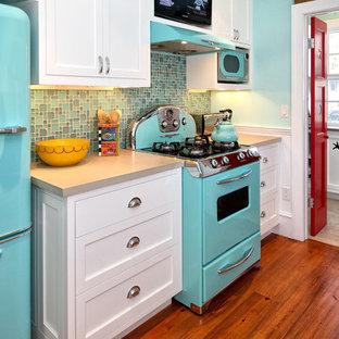 Diseño de cocina retro con electrodomésticos de colores, encimera de cemento, armarios estilo shaker y puertas de armario blancas