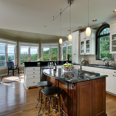 Eat-in kitchen - large traditional u-shaped medium tone wood floor and brown floor eat-in kitchen idea in DC Metro with stainless steel appliances, recessed-panel cabinets, white cabinets, multicolored backsplash and an island