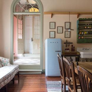 Immagine di una cucina shabby-chic style con lavello stile country, ante verdi, elettrodomestici colorati, parquet scuro e nessuna isola
