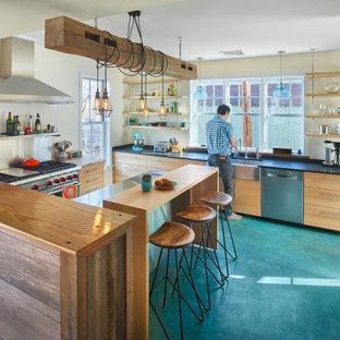 На фото: большая п-образная кухня в стиле фьюжн с раковиной в стиле кантри, плоскими фасадами, светлыми деревянными фасадами, серым фартуком, техникой из нержавеющей стали, бетонным полом, полуостровом, синим полом и черной столешницей с