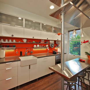 This is an example of a small eclectic galley separate kitchen in DC Metro with a farmhouse sink, flat-panel cabinets, white cabinets, concrete benchtops, orange splashback, stainless steel appliances, medium hardwood floors and brown floor.