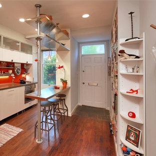 Diseño de cocina de galera, ecléctica, pequeña, cerrada, con fregadero sobremueble, armarios con paneles lisos, puertas de armario blancas, encimera de cemento, salpicadero naranja, electrodomésticos de acero inoxidable, suelo de madera en tonos medios y suelo marrón