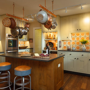 This is an example of a country u-shaped kitchen in Other with shaker cabinets, beige cabinets, orange splashback, mosaic tile splashback, stainless steel appliances, medium hardwood floors, with island and brown floor.