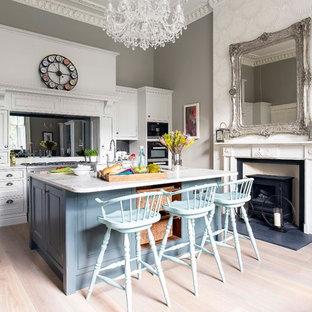Ejemplo de cocina bohemia con armarios con paneles empotrados, puertas de armario blancas, salpicadero con efecto espejo, suelo de madera clara y una isla